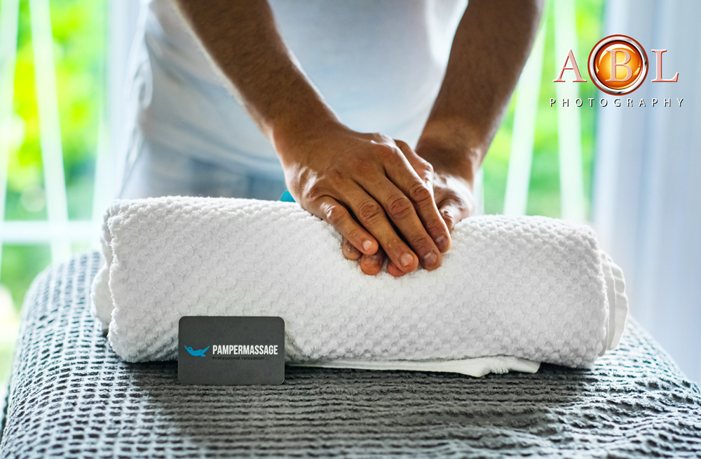 massage table with a towel and therapist's hands on top of the towel