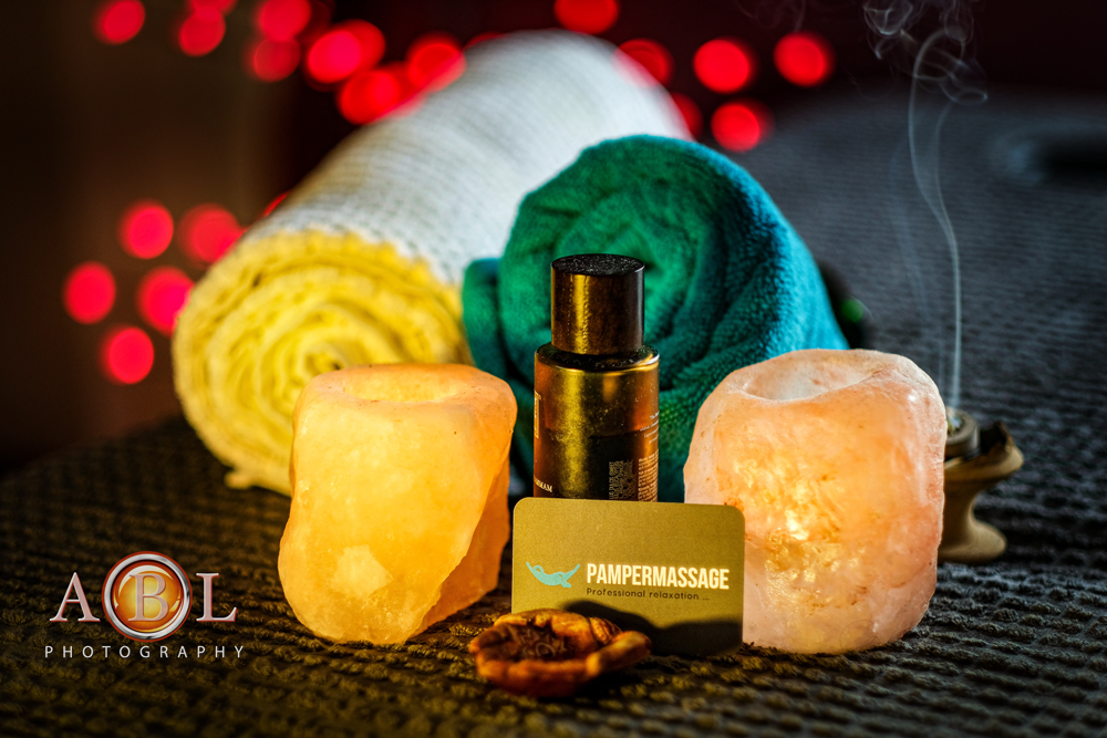candles, massage oil and Pamper Massage business card on a massage bed